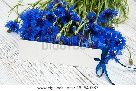 paper tag with blue fresh cornflowers on wooden table