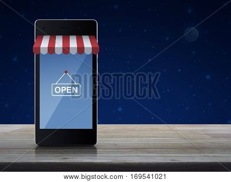 Modern smart mobile phone with on line shopping store graphic and open sign on wooden table over fantasy night sky and moon Shop online concept