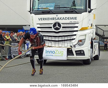 Chemnitz, Germany - October 4, 2015: A strong woman pulling a heavy truck with a rope during the FIROCON Truck Pull European Championships.