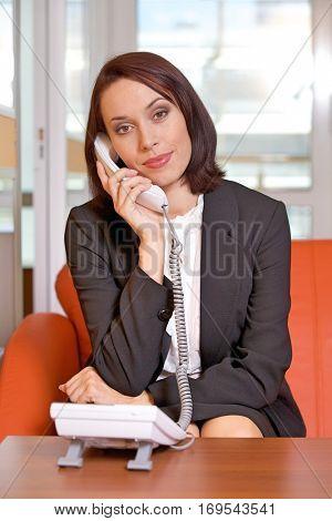 Businesswoman conversing on landline phone, portrait