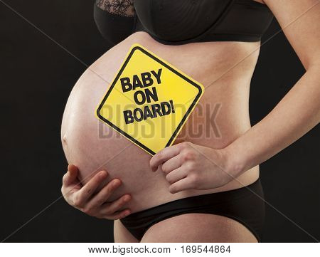A pregnant woman abdomen close-up with a sign reading baby on board.