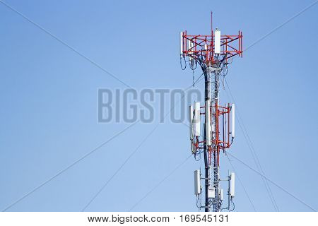 Mobile phone communication tower transmission signal with blue sky background and leash