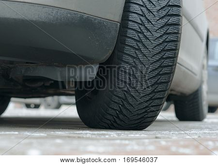 Close up of car's winter tyre tread on the road