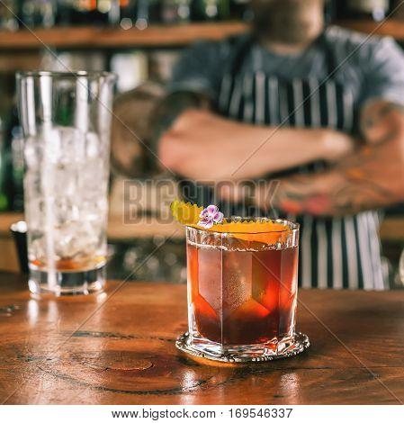 Closeup barman is making cocktail at night club. Negroni cocktail