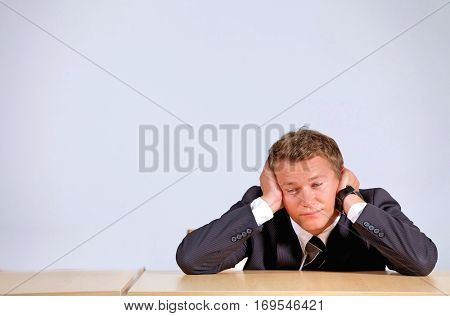 Businessman sitting with head in hands in office