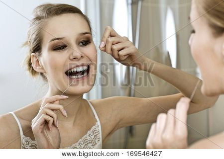 A young woman flossing her teeth