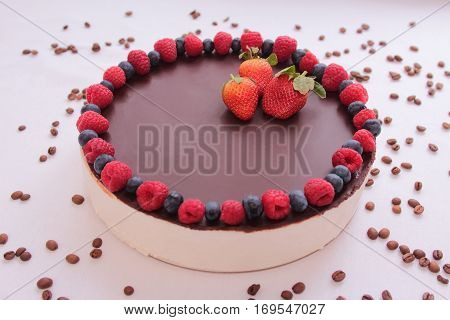 Cake souffle, covered with chocolate, jewelry, berries, raspberry, blueberry blueberry strawberry white background