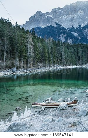 Canoe on a rocky shore of a calm blue Aibsee lake