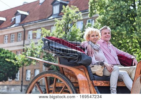 Happy middle-aged couple sitting in horse cart on city street