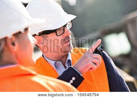 Supervisor showing something to colleague at construction site poster