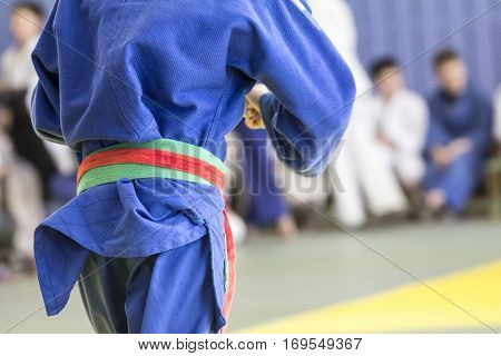 Young judoka in kimono fight on the tatami in the gym