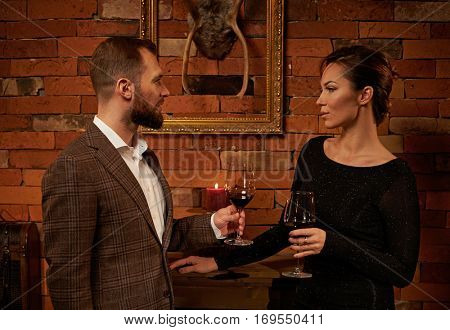 Well-dressed couple with glass of red wine in cozy home interior