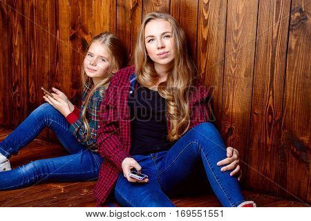 Modern generation. Two cute girls, older and younger sister sitting together on a floor with their smartphones.