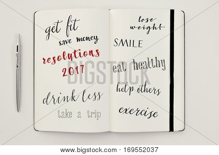 high-angle shot of a notebook with some resolutions for 2107, such as get fit, save money, drink less, take a trip, lose weight, smile, eat healthy, help others or exercise