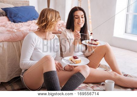 No worries, just relax. Cheerful charming young ladies eating cake as a morning meal and enjoying it while sitting on the floor near bed