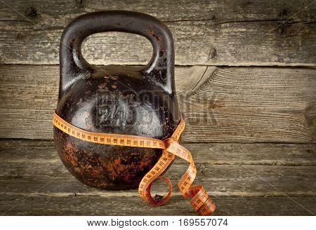 Vintage Old kettlebell on a wooden background with tape-measure. Concept fitness and diet.