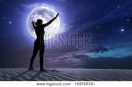 female silhouette with outstretched arms in the moonlight
