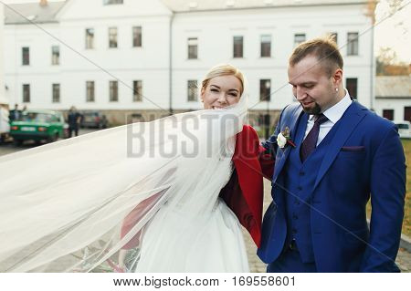 Bride Smiles With A Veil Turned Around Her Neck, Standing Behind A Groom