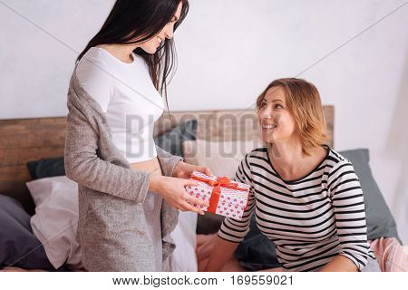 A little surprise. Graceful emotional young woman presenting her girlfriend a cute box celebrating their anniversary and staying home all weekend long