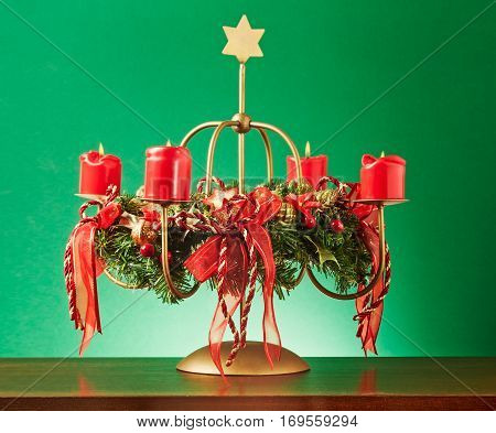 Vintage advent wreath with four burning red candles and gold star on green background lights and decoration for christmas time