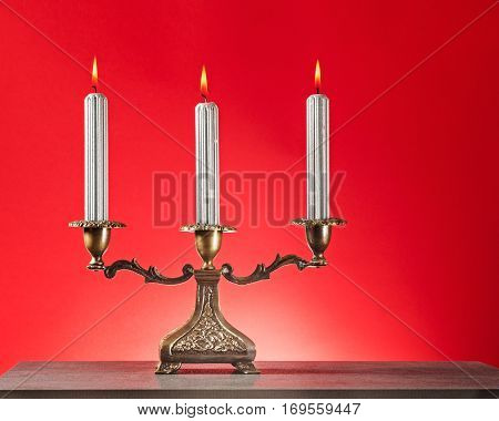 Antique bronze candlestick with three burning silver candles on rot background
