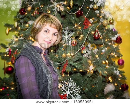 Portrait of young woman with gift around a Christmas tree decorated. Girl on holiday new year