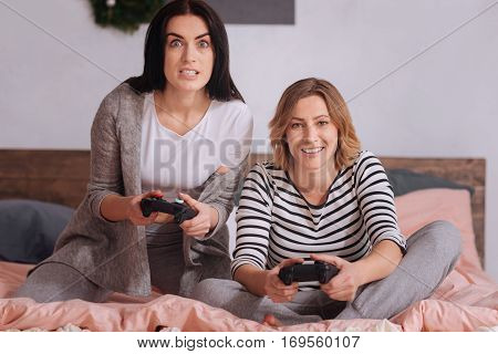 No way I can lose. Two positive charming young women sitting on the bed and having fun together while spending their weekend at home