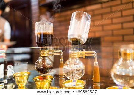 Siphon vacuum coffee maker on cafe bar