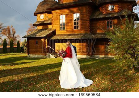 Bride Smiles Standing With A Weding Bouquet On The Backyard Of An Old Wooden Church