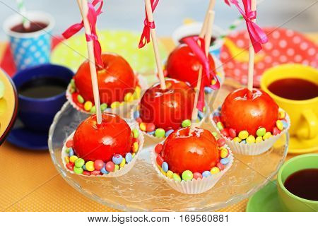 Delicious apples in caramel on stand at birthday party