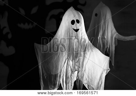 Funny ghost as decor for Halloween party, on dark background