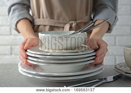 Female hands holding pile of porcelain dishware, closeup