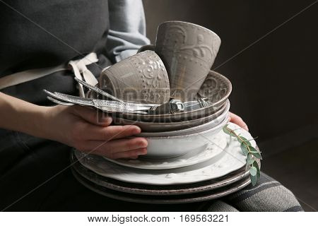 Female hands holding pile of dishware, closeup