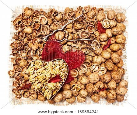 Walnut kernels in heart shaped box whole walnuts nutshells and nutcracker background as healthy eating and dieting concept top view flat lay