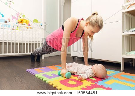 mother doing fitness and playing with her baby