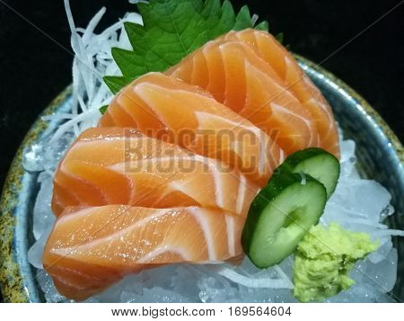 Special Deluxe salmon sashimi set on ice sever with wasabi and cucumber traditional Japanese food closed up focus salmon with blur background