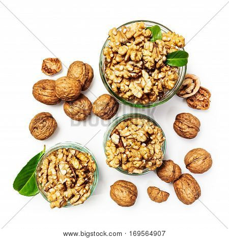 Walnut kernels in glass bowl whole walnuts and nutshells as healthy eating and dieting concept group of objects isolated on white background with clipping path top view flat lay