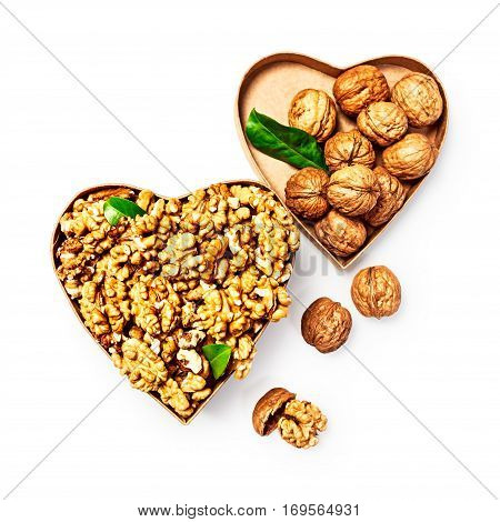 Walnut kernels in heart shaped box whole walnuts and nutshells as healthy eating and alternative medicine concept objects isolated on white background with clipping path top view flat lay