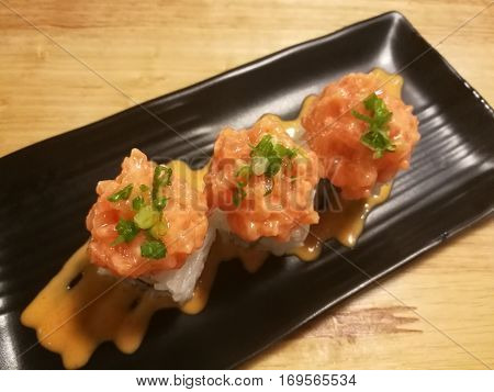 Fusion salmon sushi stuff with cucumber crab stick and mango Stylist food medium shot