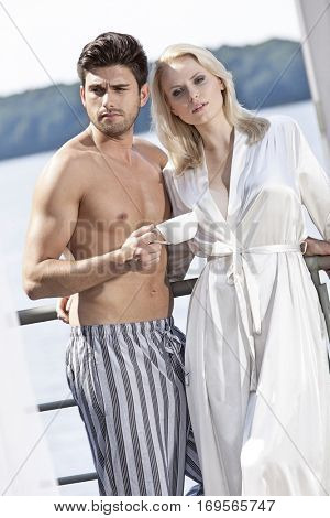 Young couple in sleepwear having coffee on hotel balcony