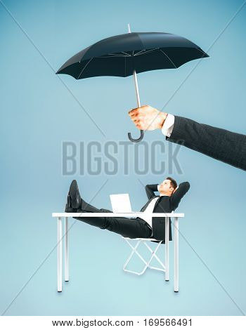 Hand holding umbrella over businessman relaxing at workplace. Safety concept. Blue background