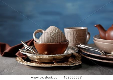 Brown dishware on table and colour background