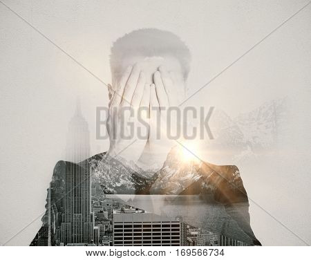 Man covering face with hands on abstract city and nature background with sunlight. Fear concept
