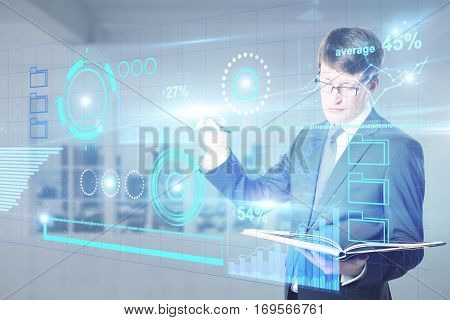 Attractive caucasian man with open notepad drawing creative business charts and diagrams. Online accounting concept