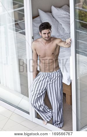 Full length of shirtless young man standing at balcony doorway
