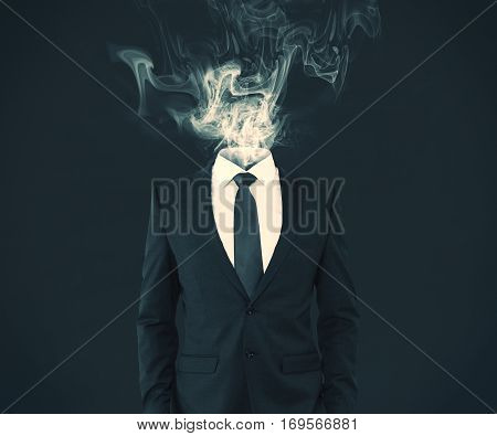 Businessman with smoke intead of head on dark background. Lost concept