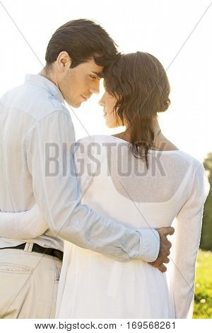 Rear view of romantic couple standing arms around against clear sky