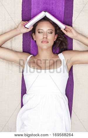 Young woman with eyes closed holding book while lying on picnic blanket