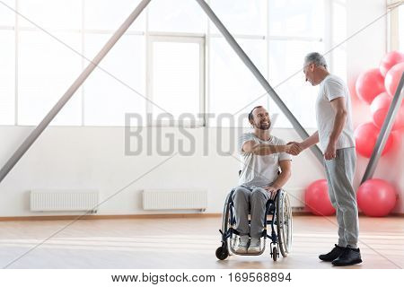 Our first meeting. Delighted positive cheerful physical therapist greeting his patient and standing in the gym while expressing positivity