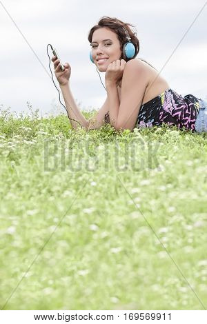 Side view portrait of woman listening to music through cell phone using headphones while lying on grass against sky